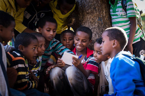 A group of boys smiles and reads a letter