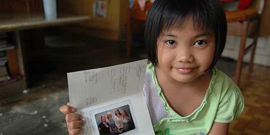 An Indonesian sponsored child holds up a letter from her sponsor.