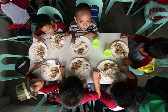 Children sitting around a table eating their meal at school