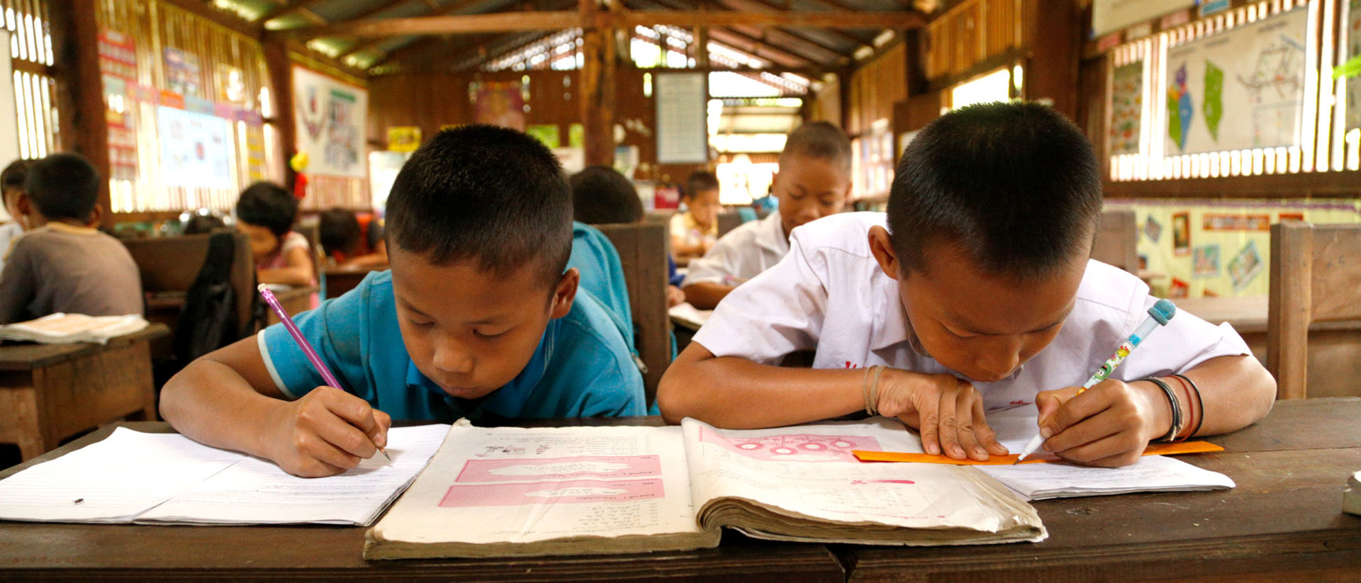 Songwut, right, and a classmate study in their village's wooden schoolhouse.
