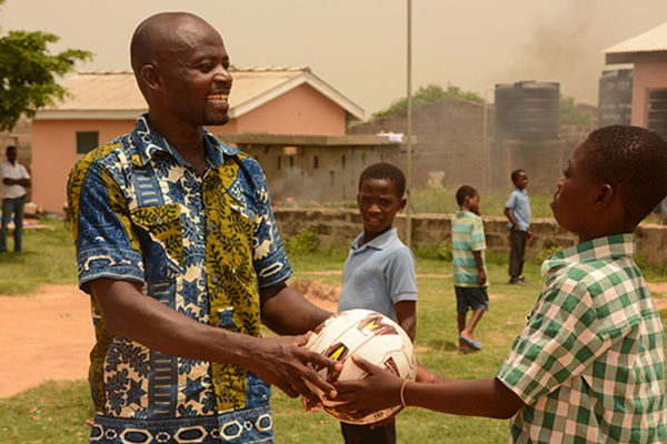 Henry giving a young boy a soccer ball.