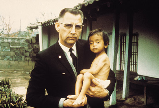 Rev. Everett Swanson holding a Korean orphan