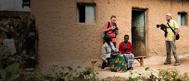 Photographers interact with some beneficiaries in front of a home