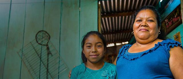 A woman in blue has her arm around a young girl wearing teal