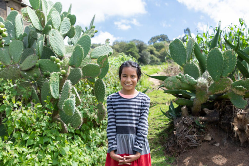 A girl stands in front of cactus and smiles