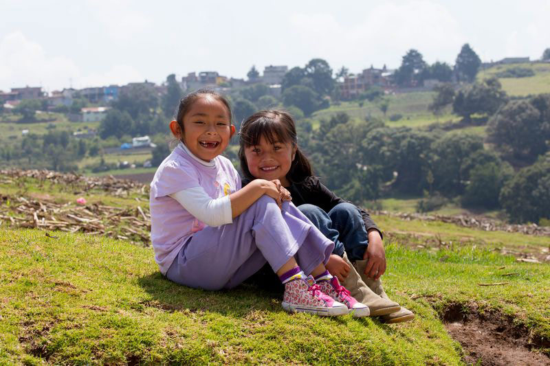 Two girls sit on a hill with mountains behind them