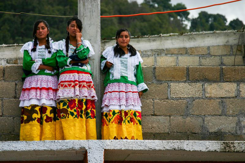 Three teenage girls dress in traditional Mexican outfits