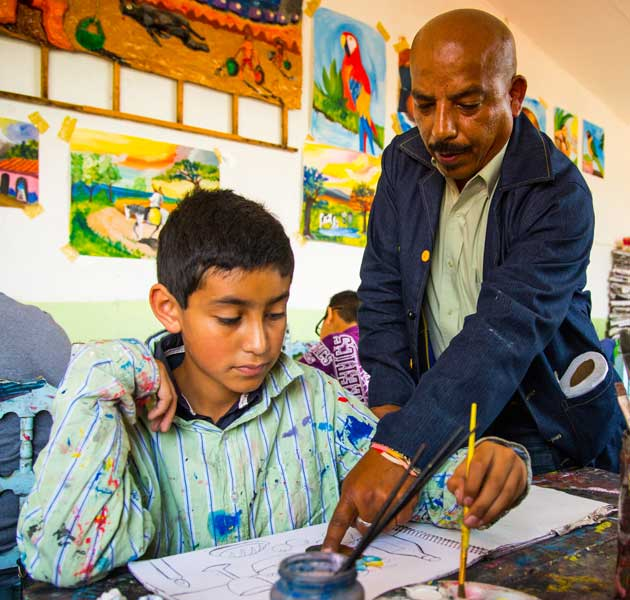 A teacher helping a boy with his art project