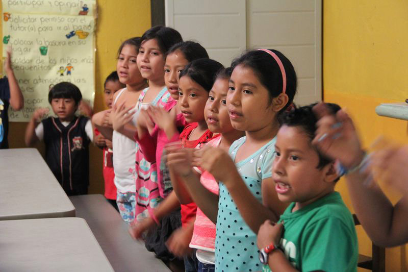 Children stand singing and clapping in class