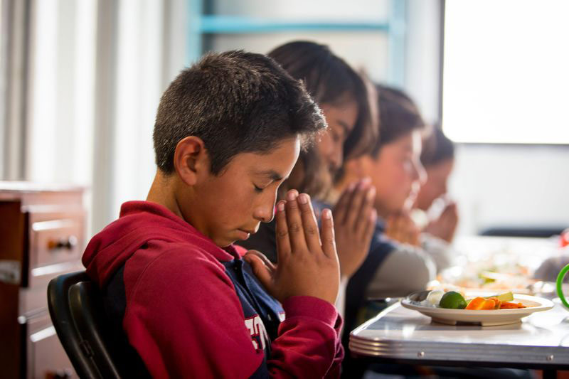 Children pray before a meal