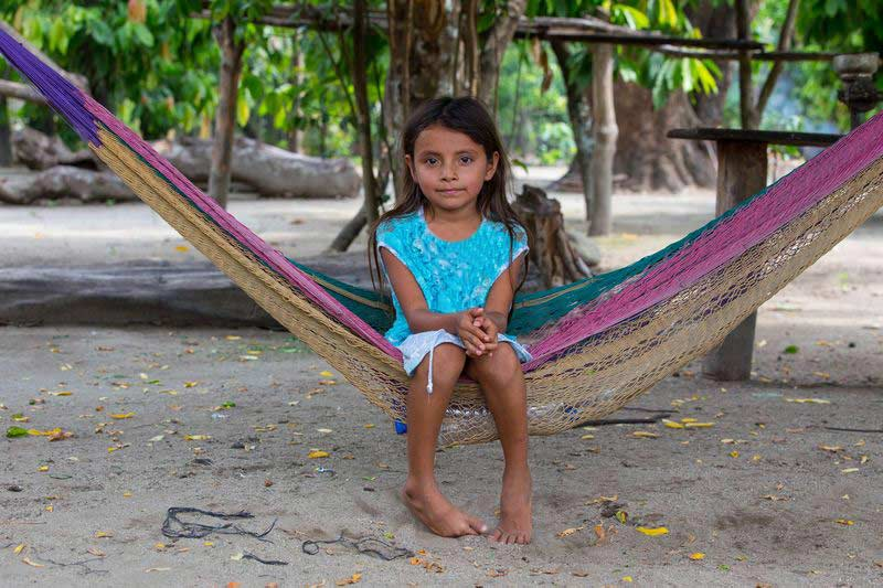 A girl sits in a hammock and smiles