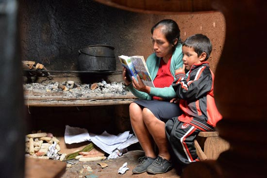 A mom reading the bible to young boy