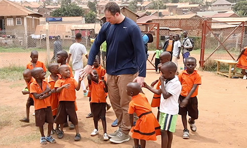 Nate Solder playing with a group of Compassion children