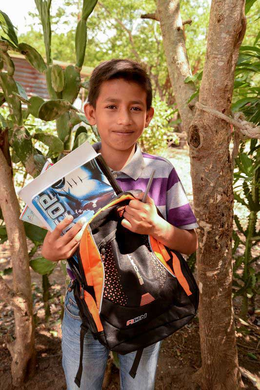 A young boy holds his schoolbooks and backpack in his hands