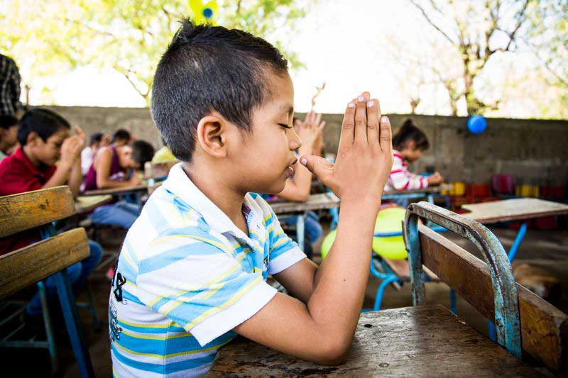 A young boy holds his hands together to pray during a lesson