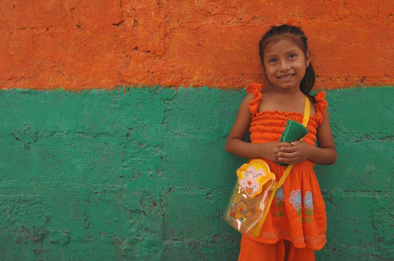 A young girl smiles in front of a colorful wall
