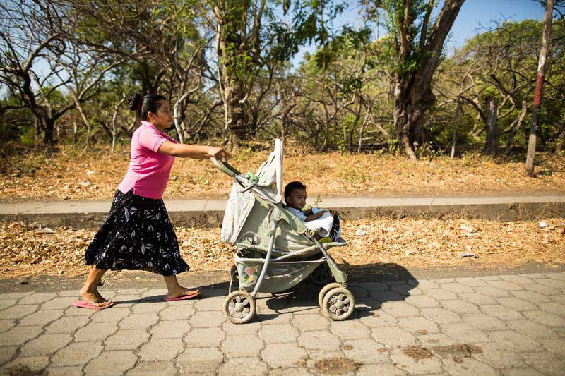 A mother pushes her baby in a stroller