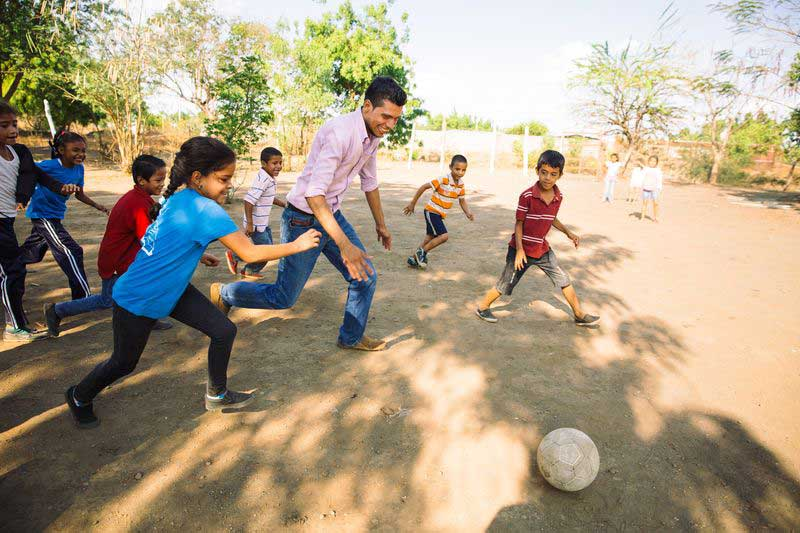 The local pastor plays soccer with children at the child development center