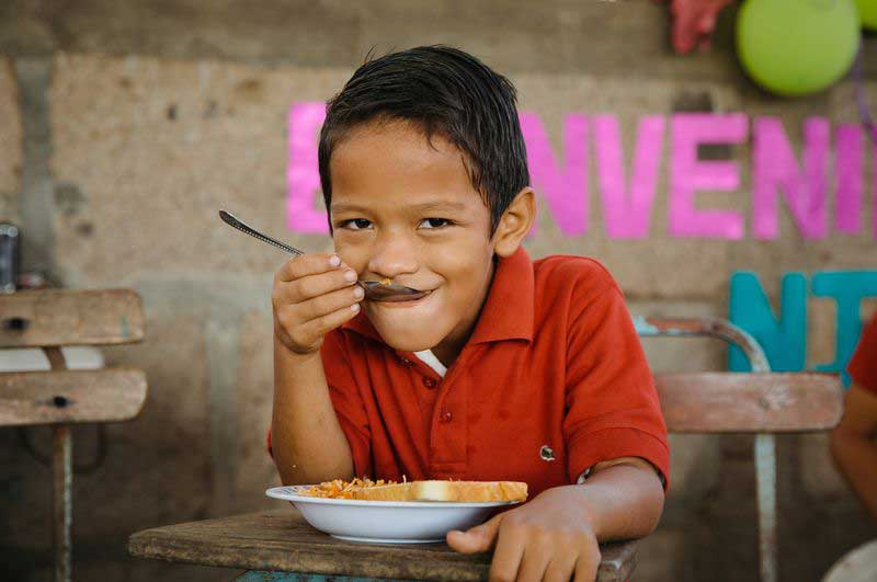 A young boy smiles as he enjoys a nutritious meal