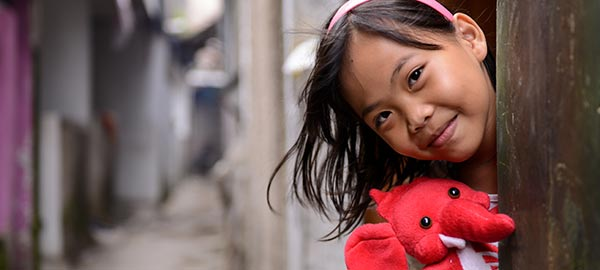 A girl holding a red stuffed elephant peaks her head out from behind a pole