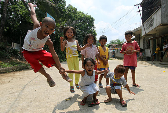 A group of Filipino children holding hands and jumping