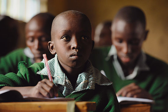A young Kenya boy in a green sweater sits at a school desk and writes.
