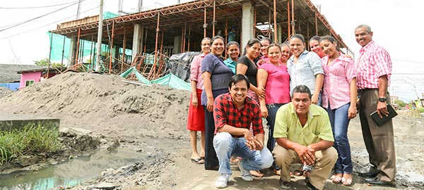 a group of people standing in front of a building being built