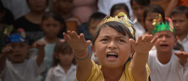 A young girl wearing a paper crown stretches her arms out in front of her