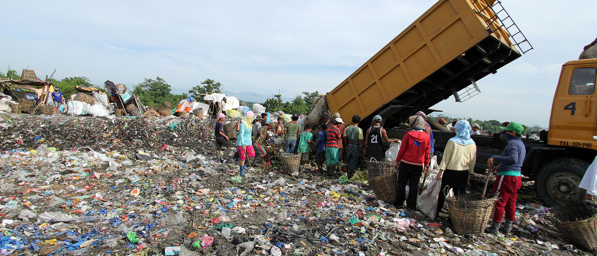 People standing in line waiting for a new load of garbage from the dumptruck