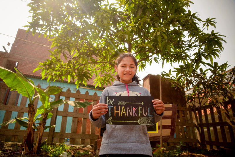 "A young lady holds up a sign saying ""Thankful"""