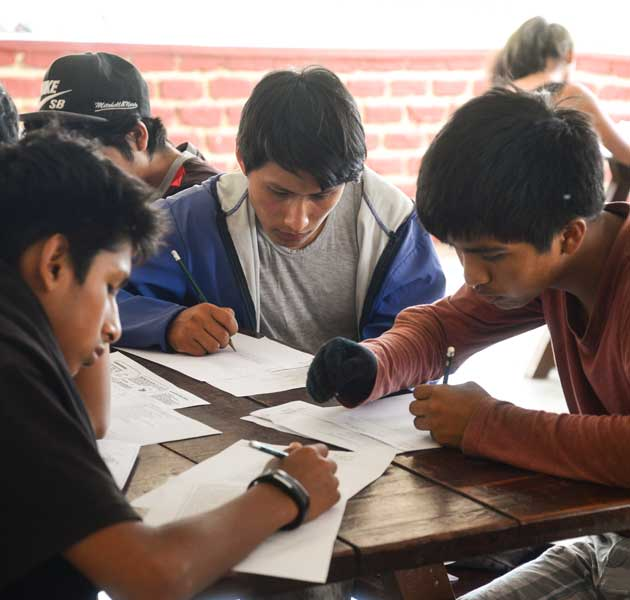 A group of boys working on their school work together