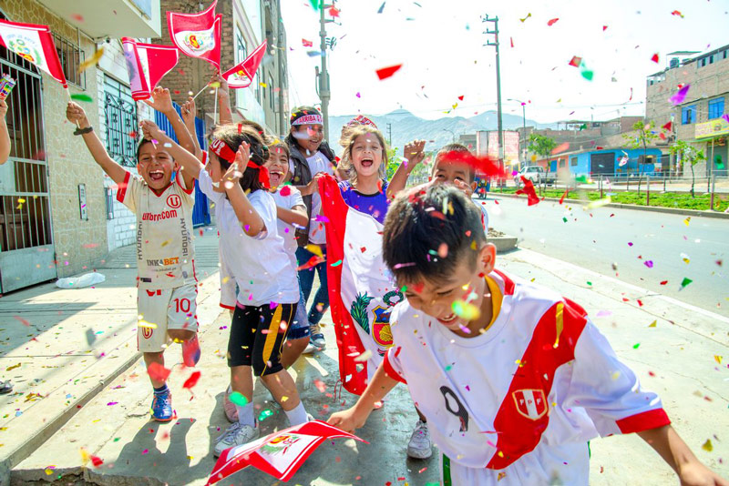 A group of children run through their neighborhood with confetti and Peruvian flags