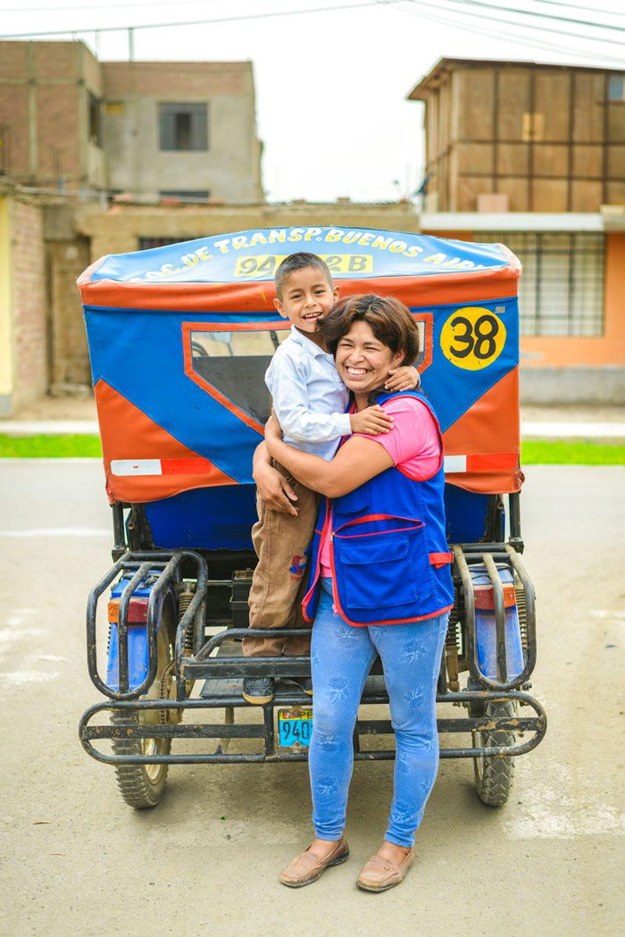 A boy and his mother stand near her red and blue taxi