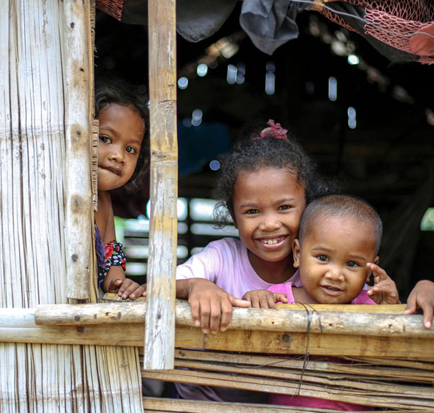 Three children smile while looking out a window in their home.