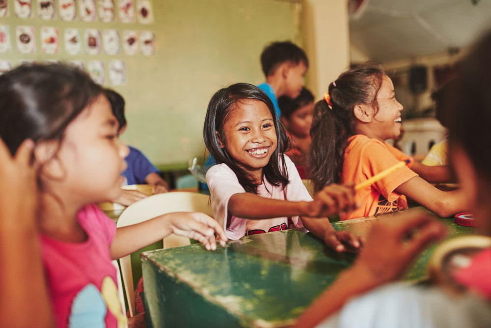 Children smile, laugh and play together in a classroom at their child development center