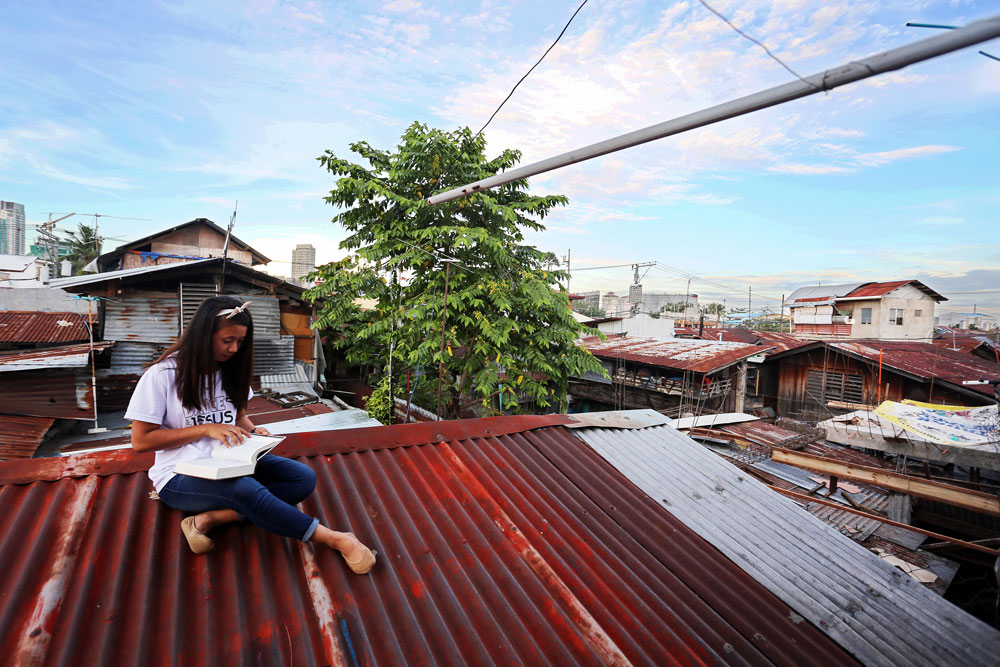 A girl sits on a rooftop reading