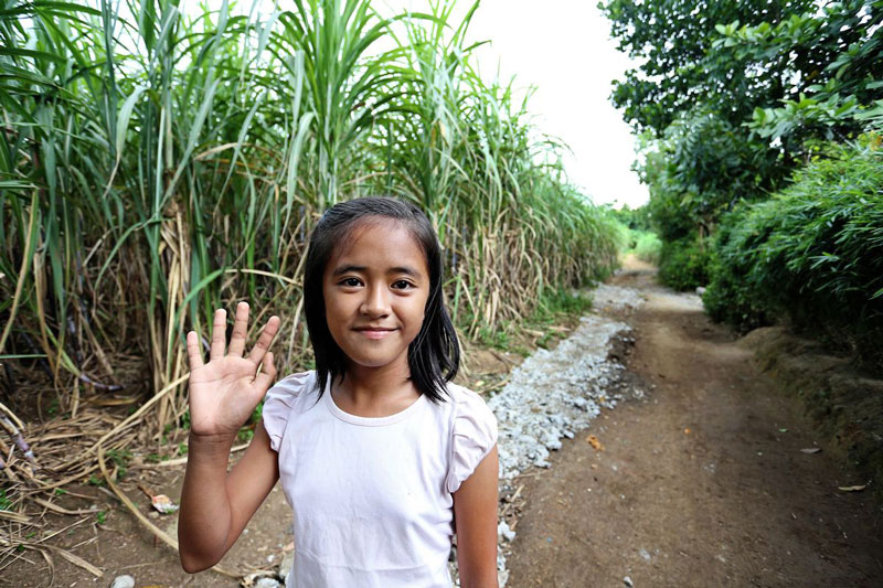 A girl smiles and waves while standing on a dirt path