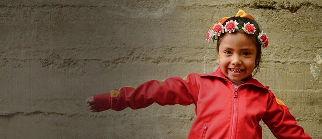 A young girl in a red jacket and a white flower crown stands in front of a cement wall with her arms spread out