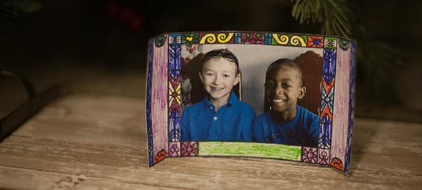 A homemade picture frame with a picture of two boys in blue shirts