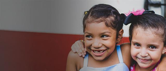 Two young smiling girls who live in extreme poverty in El Salvador