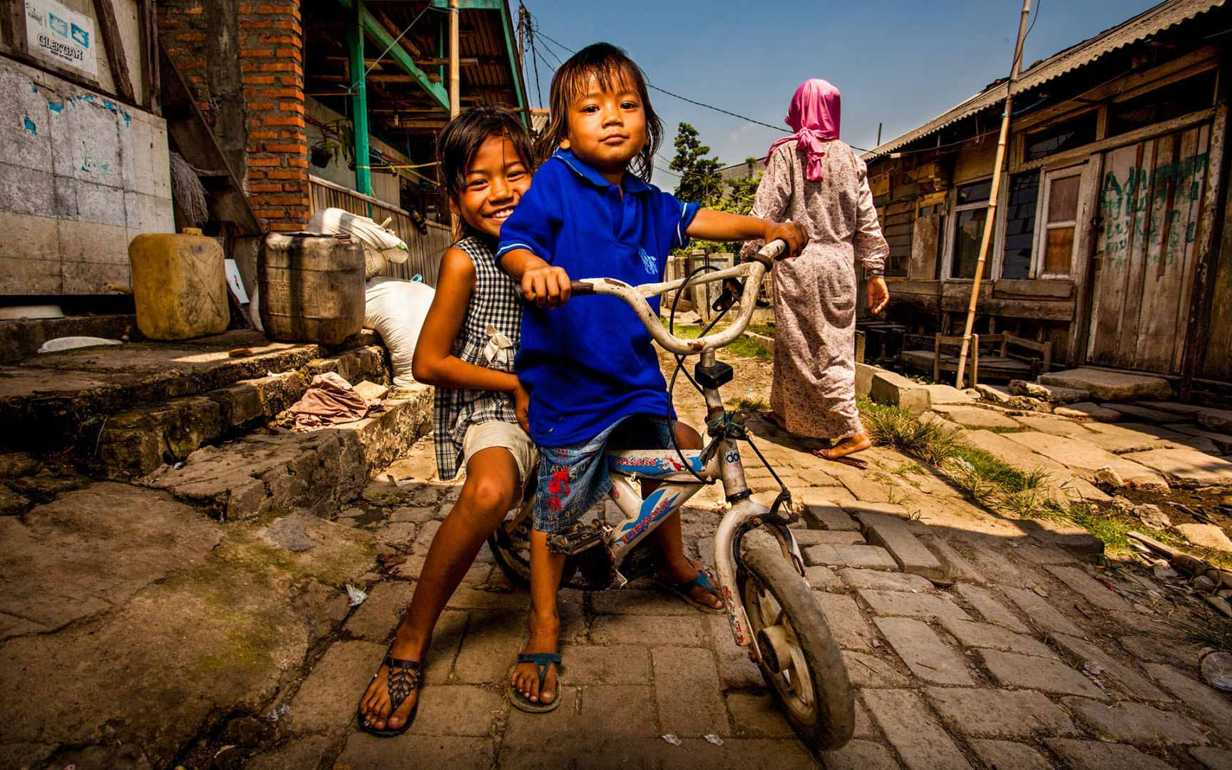 Two children sitting on a bicycle