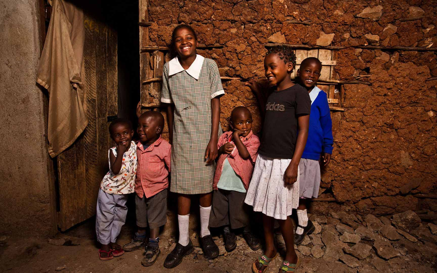 A teenage Kenyan girl and her siblings stand outside their home