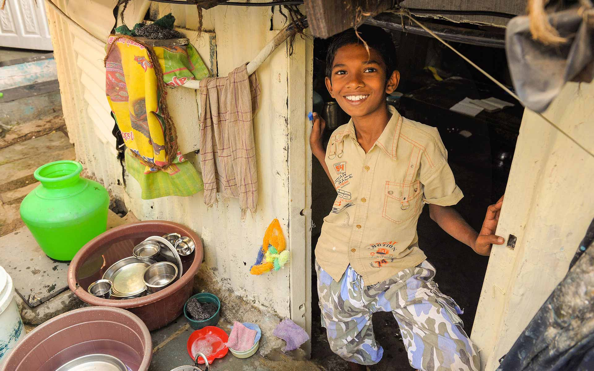 An Indian boy stands in the doorway of his home