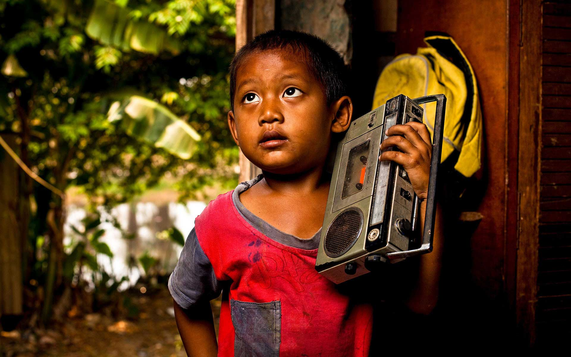 A boy holding a radio against his shoulder