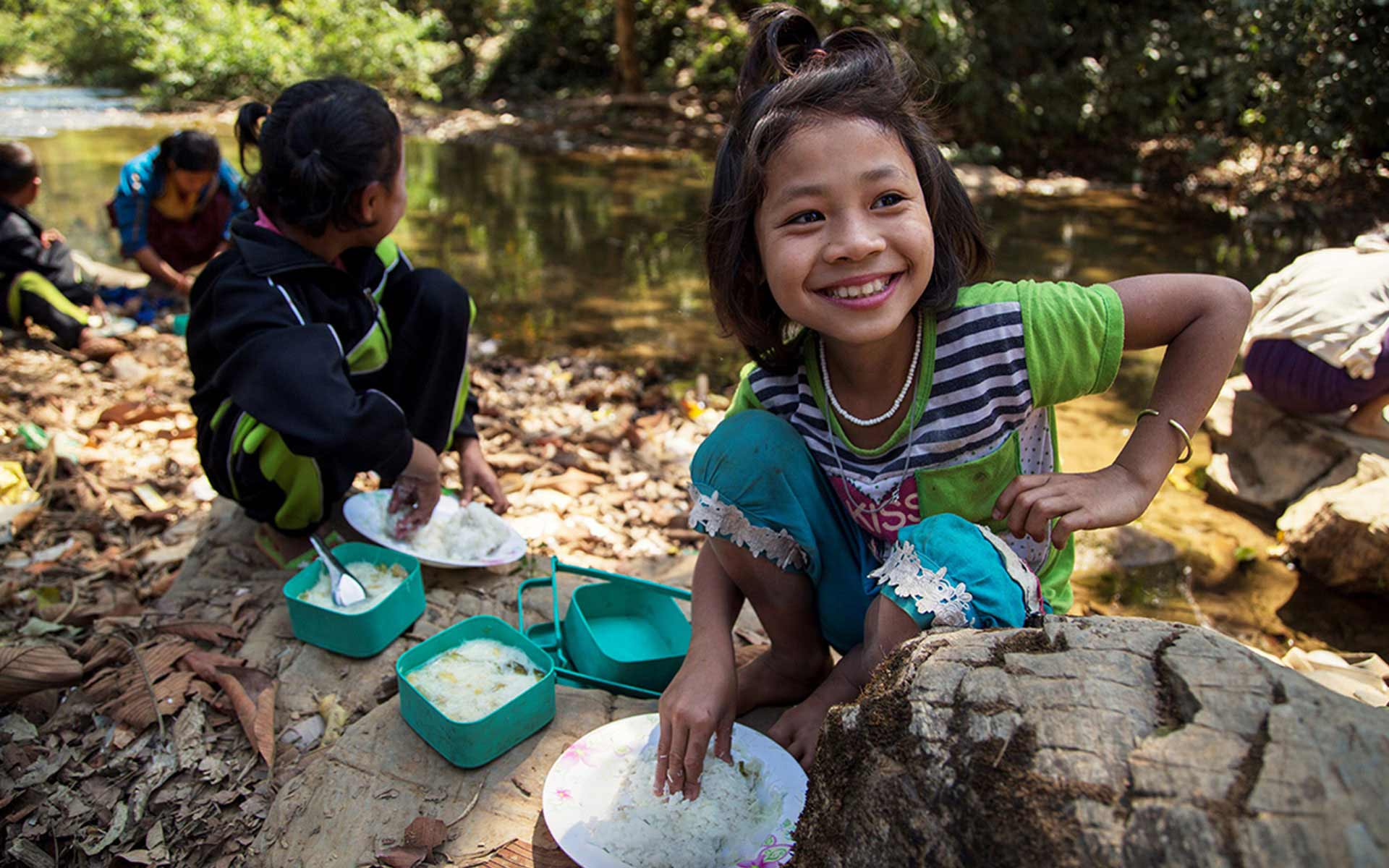 A girl from Myanmar enjoys a meal with rice