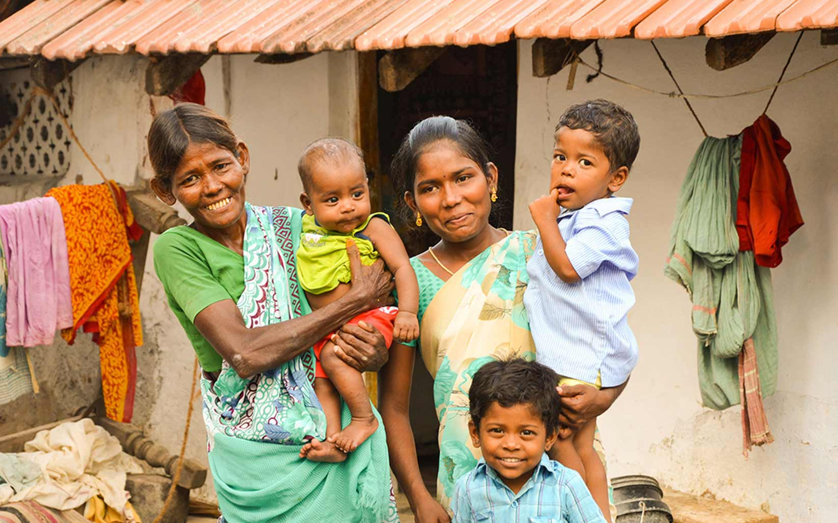 Vennila holds her son while standing with the rest of her family