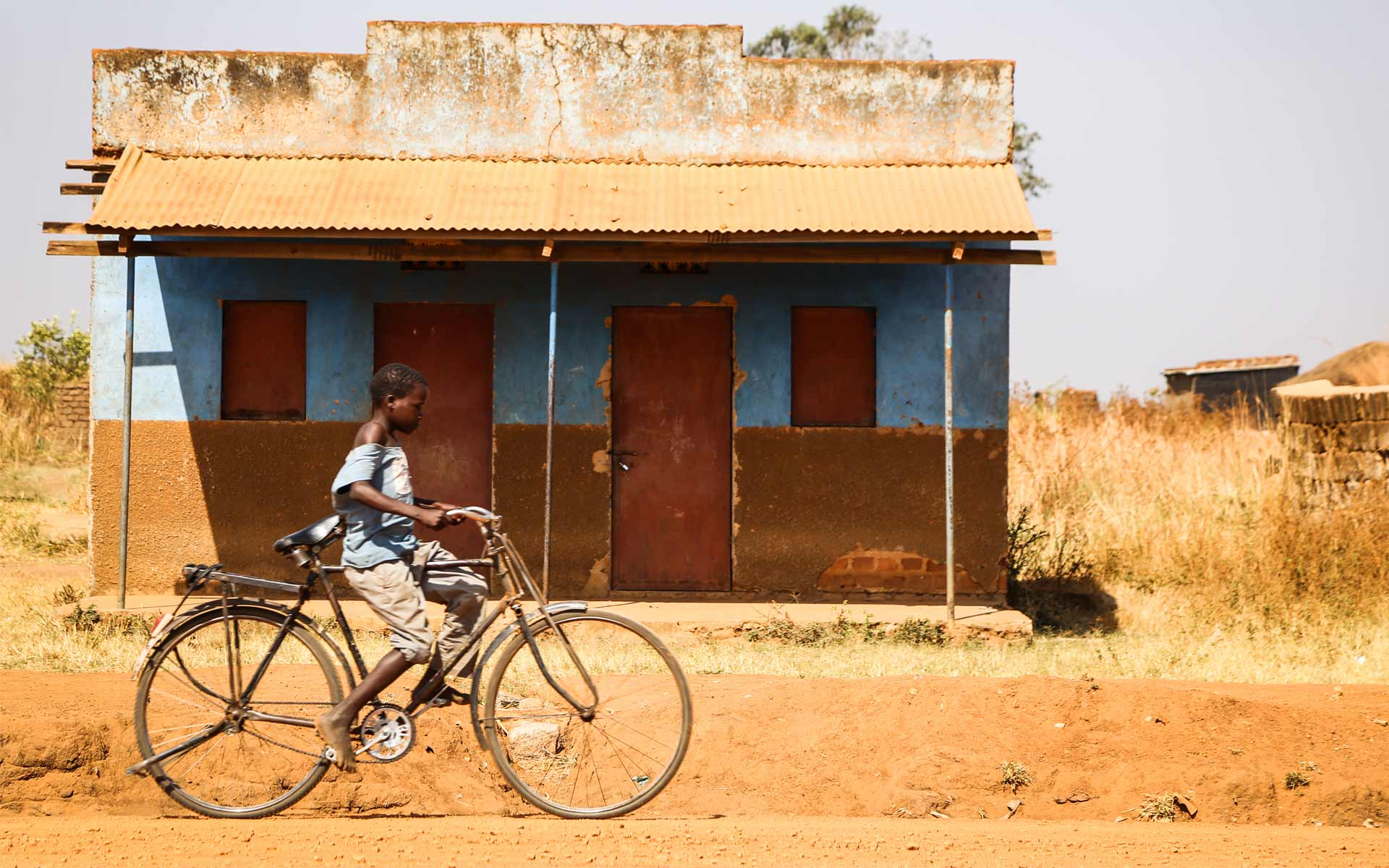 A boy in Uganda riding his bicycle
