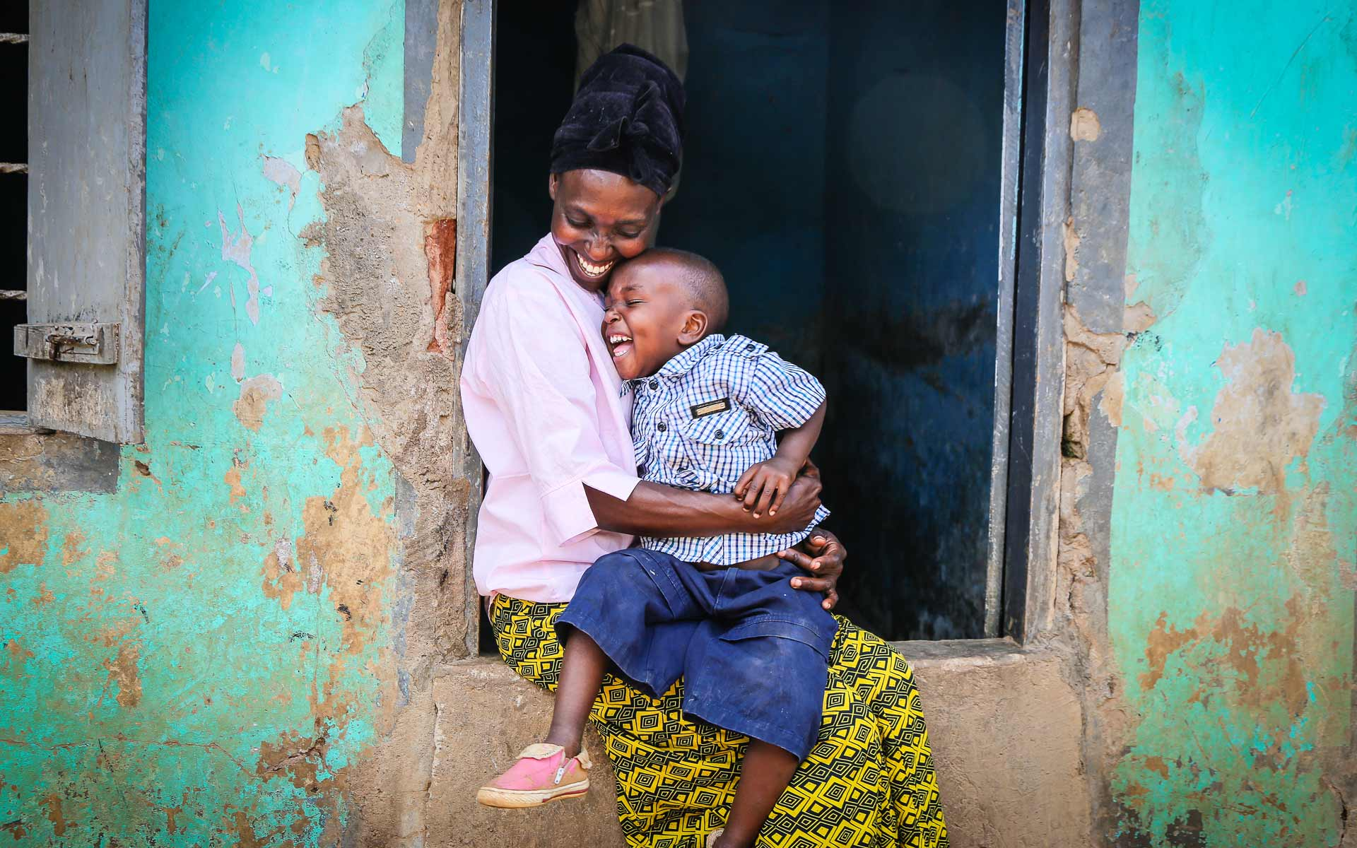 A mom holds her son who attends a Compassion Child Survival Program in Uganda