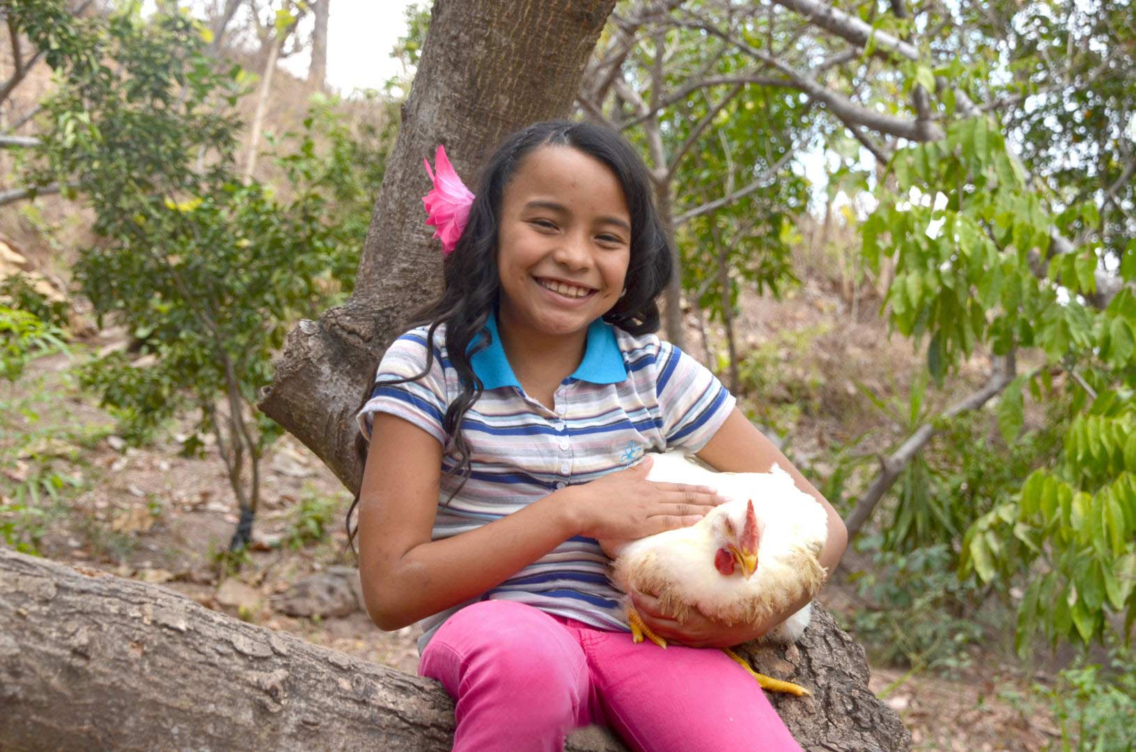 A ten-year-old girl holds a chicken from her family's business