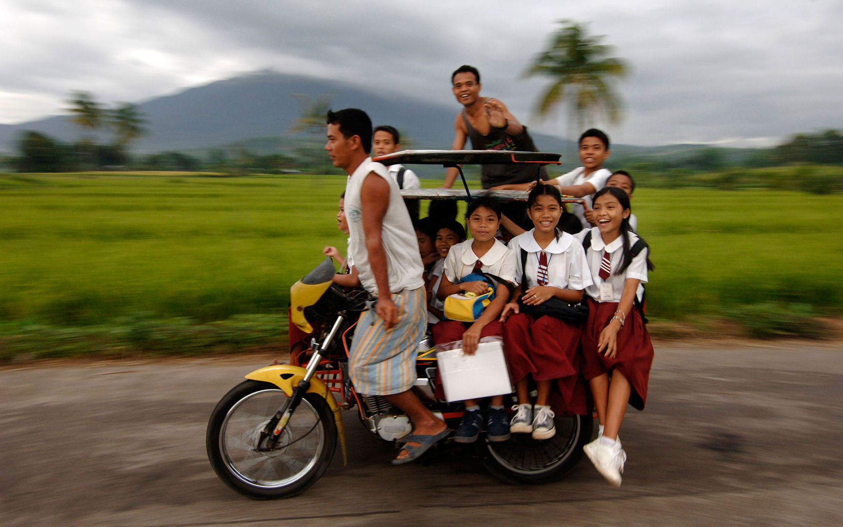 Children ride a motorcycle taxi to school